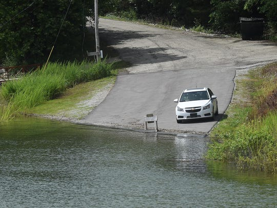 A vehicle sits by the edge of the water entering Quarry Marina's parking lot at Norfork Lake on Wednesday. High water has impacted several access and launch ramps on Norfork and Bull Shoals lakes.