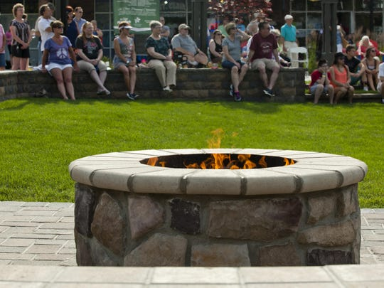 A gas fire pit is lit during the grand opening of the Riverview Plaza courtyard Thursday, June 18, 2015 in St. Clair.
