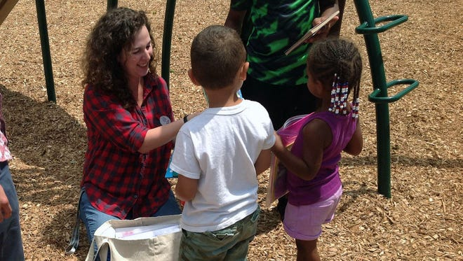 Katie Lehman, Early Literacy Coordinator at MPL, visits a local park to distribute information about the Early Literacy Program to children and their parents.