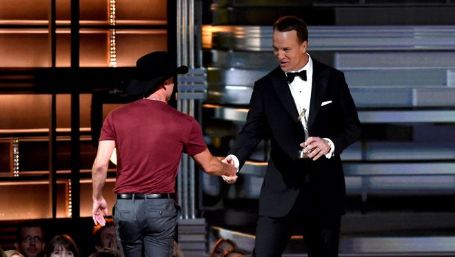 Peyton Manning presents Kenny Chesney with the Pinnacle Award onstage at the 50th annual CMA Awards Wednesday at the Bridgestone Arena in Nashville, Tennessee.