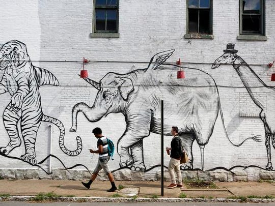 High school students Brian Scott, left, and R. J. Radcliffe walked along Pope Street next to a mural on the side of the Hilltop Tavern.