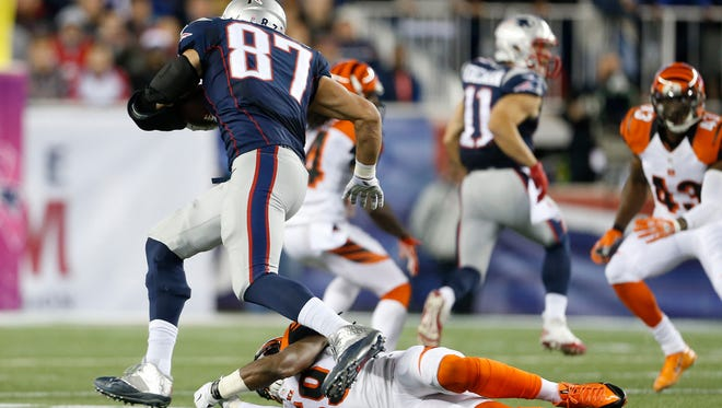 New England Patriots tight end Rob Gronkowski (87) runs past Cincinnati Bengals outside linebacker Emmanuel Lamur (59) to score a touchdown against the Cincinnati Bengals during the first quarter of their game played at Gillette Stadium in Foxborough, Massachusetts Sunday October 5, 2014. The Enquirer/Gary Landers