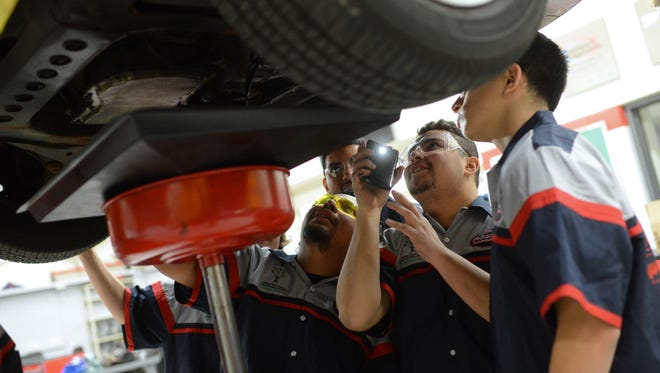 Jamie Hernandez uses his cell phone flashlight to light the underside of one a classmate's 2004 Chevrolet Cavalier as they change the oil and put in a new oil filter at City Stadium Automotive.