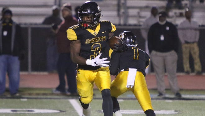 Starkville Yellowjacket running back Rodrigues Clark takes the handoff from Malik Brown in the first quarter against the Madison Central Jaguars Friday night.