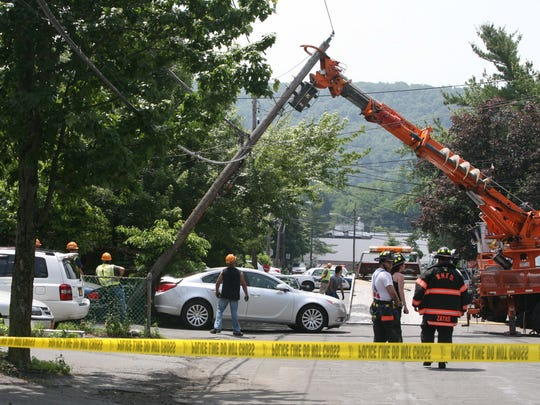 Firefighters, police and an Orange and Rockland utility crew work at the scene of a car accident in front of 35 Kennedy Drive in West Haverstraw, June 17, 2014.  The car drove into unit 35 then backed out hitting the utility pole across the street, toppling the pole and wires.