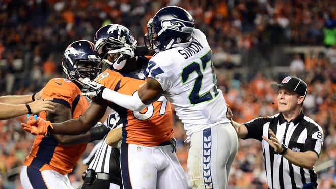 Seattle Seahawks cornerback Tharold Simon (27) hits Denver Broncos tight end Gerell Robinson (89) across his face in the third quarter of a preseason game at Sports Authority Field at Mile High. The Broncos defeated the Seahawks 21-16.
