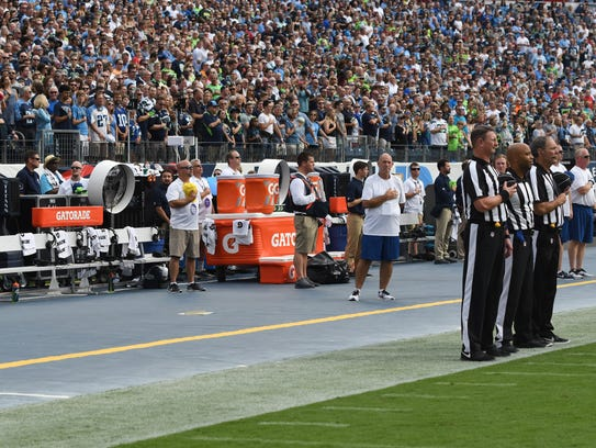 The officials stand during the national anthem in front of a Seahawks bench without players or coaches prior to the beginning of the game at Nissan Stadium on Sept. 24.