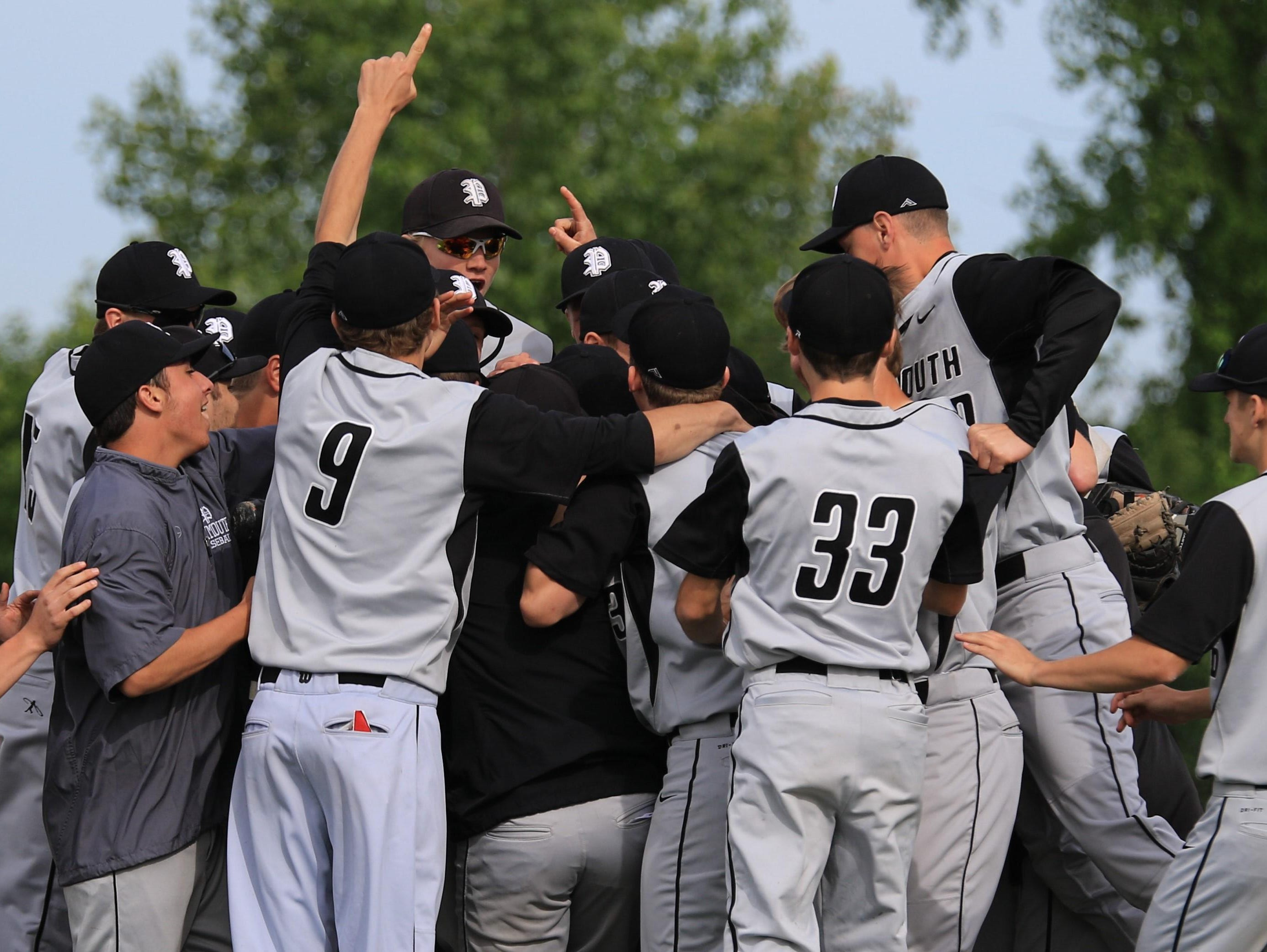 Plymouth baseball players mob each other after winning Monday's Division 1 district championship, 2-1, over Westland John Glenn.