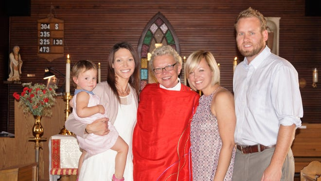Susan Hutchins, center, stands with her daughters Abigail Trumdo, left and Lindsey Zeigler with son-in-law Justin Zeigler after the ceremony welcoming her as the first female priest in Deming.