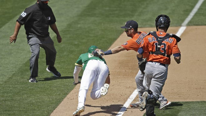 The Astros' Alex Bregman tags out Oakland's Mark Canha during a rundown in the sixth inning Saturday.