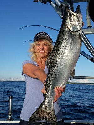 Connie McCrumb displays a Lake Michigan Chinook (king) salmon. Reductions in salmon stocks are causing disagreement among anglers.