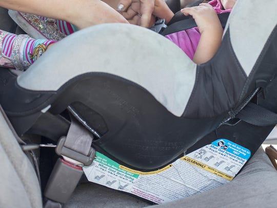 Heidi Kim abrocha a su hija Rosalind Kim de dos años en su asiento de seguridad, tras asistir a una revisión de asientos infantiles en Tucson el 25 de junio del 2015.