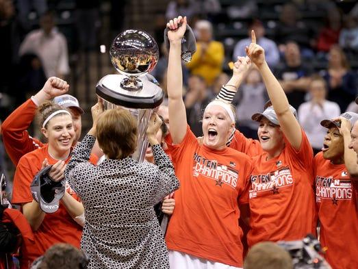 Nebraska Cornhuskers head coach Connie Yori hands the Big Ten Tournament trophy to her team. Nebraska defeated Iowa 72-65 to win the Big Ten Women's Basketball Tournament Sunday, March 9, 2014, at Bankers Life Fieldhouse.