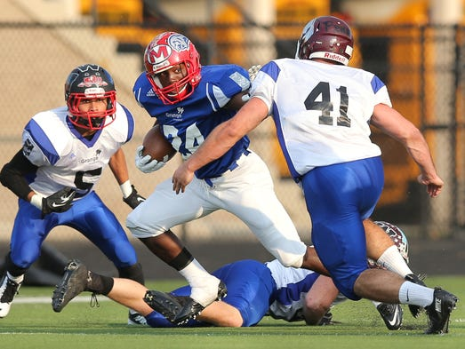 South's Taylor Sanders of Pike breaks through the North defense and defender Tony Perigini of Concordia Lutheran after a catch during the Grange All Star Football Classic held at North Central High School on Friday, July 18, 2014.