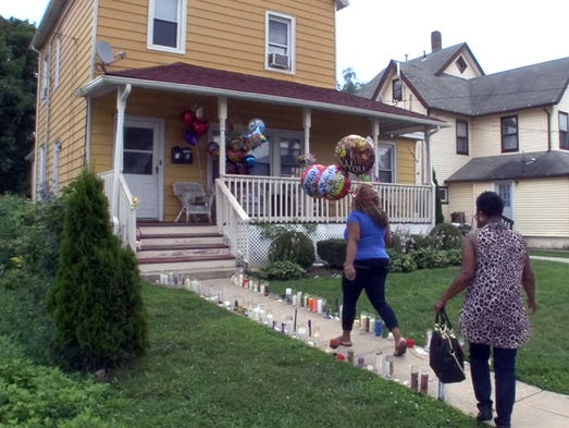 Women arrives at 61 Lippincott Avenue in Long Branch Monday morning, August 4, 2014, to leave balloons there.   A woman and girl were found dead in the first floor apartment here Friday night.