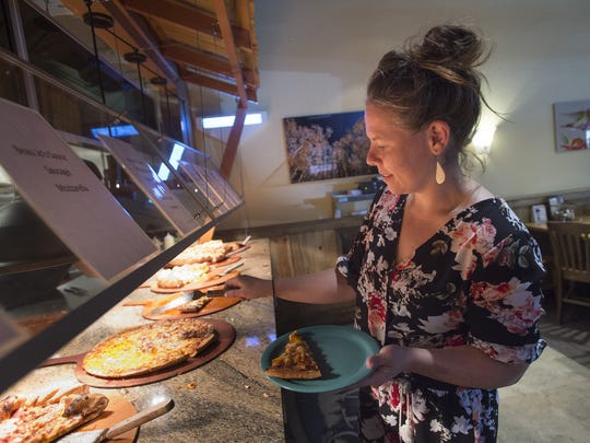 Elly Raisi chooses slices of pizza from the buffet