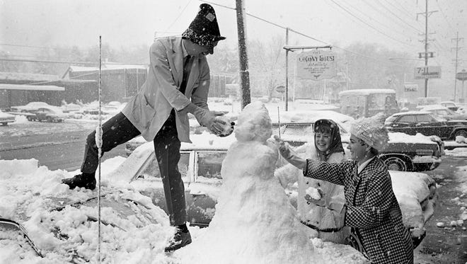 Roger Prince, left, Judy Campbell and another friend take advantage of the 5-inch snow in Nashville to build a snowman atop a car parked along Hillsboro Road Nov. 2, 1966.