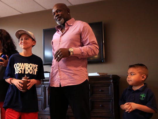 Former Dallas Cowboys player Emmitt Smith watches A.J. Gonzalez (left), 12, and Sebastian Cardenas, 7, take turns throwing a football with other kids Thursday, Sept. 7, 2017, at the Ronald McDonald House Charities of Corpus Christi. Smith is this year's Casa de Amor Gala featured speaker.