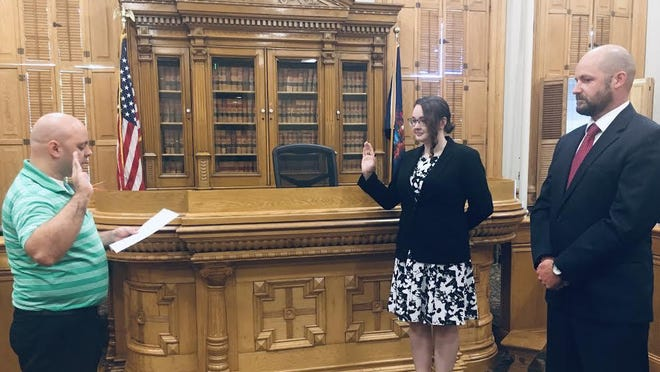 Ionia County Clerk Greg Geiger, left, swears in Ionia County Assistant Prosecutor Allison Witte on July 6 as Ionia County Prosecutor Kyle Butler, right, looks on.
