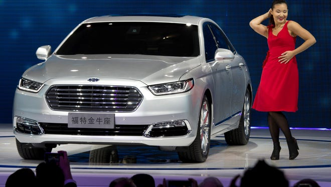 In this Monday, April 20, 2015 photo, Ford unveils the new Taurus during the Shanghai Auto Show in Shanghai. With its newest Taurus, Ford is joining the race to appeal to Chinese business buyers by offering bigger, more luxurious back seats.