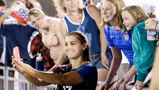Alex Morgan poses for pictures with fans following the United States' match on June 2 in Denver, a 3-3 tie against Japan in which she scored twice.