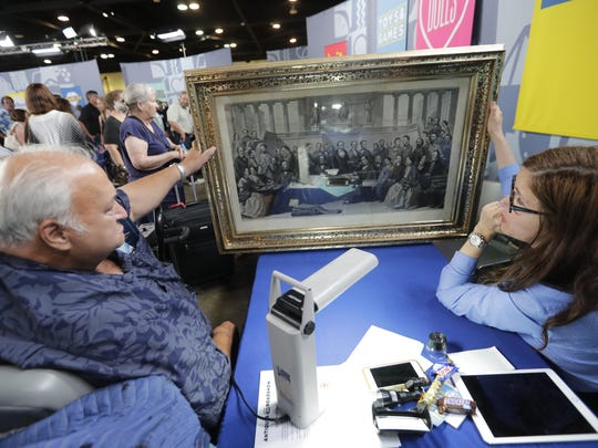Antiques Roadshow art expert Laura Ten Eyck of Argosy Gallery in New York City, right, evaluates a 19th-century engraving of American authors owned by Karl S. of Chicago Saturday, June 17, 2017, when the PBS show visited the Resch Center in Ashwaubenon, Wisconsin.