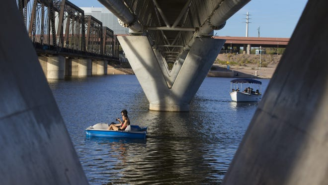 Wayne Ching, 32, of Tucson, and Hop Le, 29, of Mesa, enjoy the nice weather while paddling in Tempe Town Lake on Jan. 27, 2018.