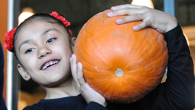 Charlee Cuevas, 7, balances her pumpkin on her shoulder on Friday after receiving it for free from Crop Production Services.