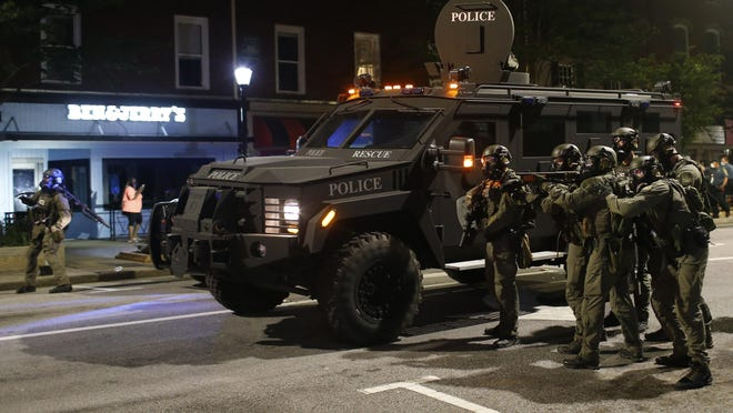 Athens-Clark County police officers in riot gear, backed up by a military vehicle, move to remove protesters from Broad Street in downtown Athens after a protest in response to George Floyd's death Sunday.