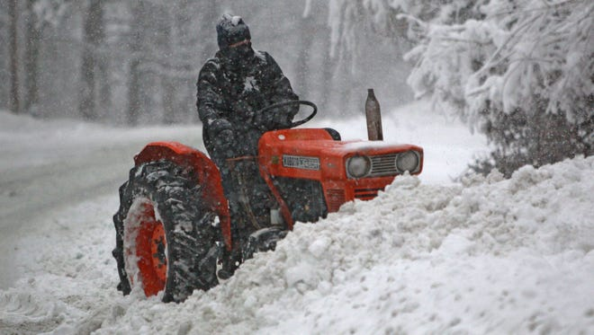 A tractor plows snow from a drive along Kessler Boulevard on Jan. 5, 2014.