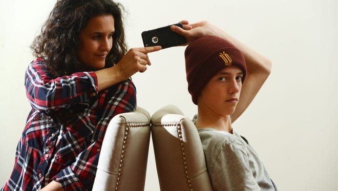 Simone Noble and her son Jonah Jowell, 12, create a caricature of their relationship when it comes to his smartphone usage at home in Ojai on Monday.