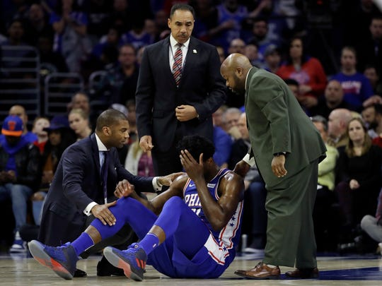 Philadelphia 76ers' Joel Embiid, center, lies not he court after an injury during the first half of an NBA basketball game against the New York Knicks, Wednesday, March 28, 2018, in Philadelphia.