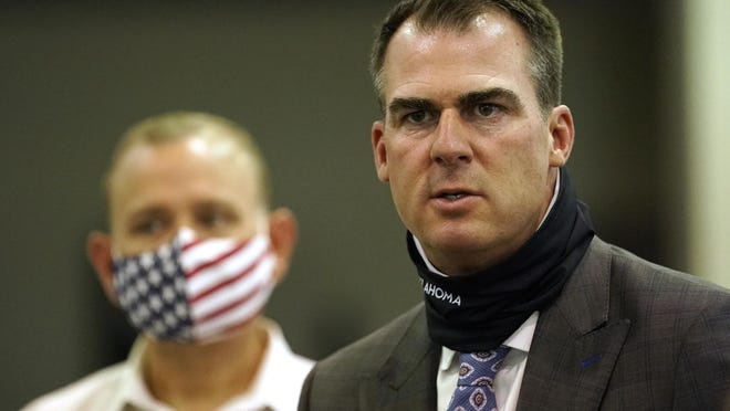 Oklahoma Gov. Kevin Stitt answers a question during a news conference at the Central Oklahoma PPE distribution warehouse Tuesday, Aug. 18, 2020, in Oklahoma City.