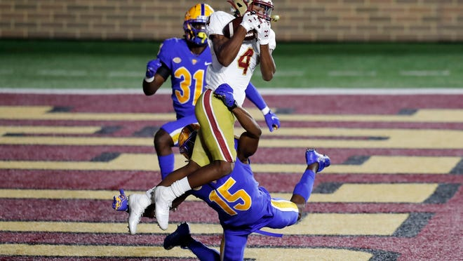 Boston College wide receiver Zay Flowers (4) makes a touchdown reception over Pittsburgh defensive back Jason Pinnock (15) in overtime Saturday.