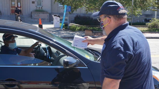 David Deloge, EMA director of Pawtucket and Central Falls, hands a packet of masks to a driver in front of City Hall.