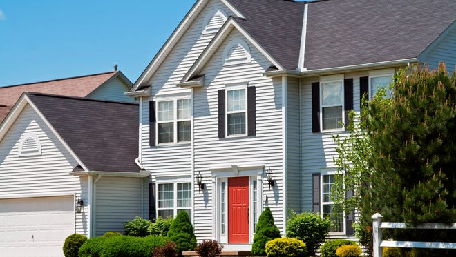 A house with a bright red front door. Designers suggest using a pop of color to draw attention to your front door.