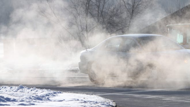 Cars drive through clouds of exhaust fumes that are more apparent because of the bitter cold in Rochester in March.