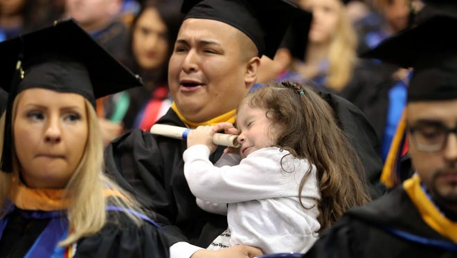 Manuel Llivisaca of Tarrytown sits with his daughter Mia, 4, who found her own use for her father's diploma during commencement ceremonies at Pace's Pleasantville campus May 16, 2018.