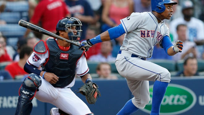 Mets outfielder Curtis Granderson (right) follows through on a two-run home run as Atlanta Braves catcher Christian Bethancourt looks on in the third inning Tuesday.
