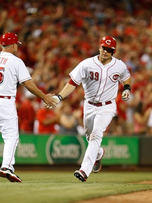 Reds catcher Devin Mesoraco is congratulated after a solo home run on July 11.