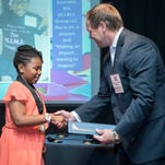 Michael MacFarland, regional vice president for TD Bank, presents Naomi G. Jones, 10, of Bridgeton, with a special medal and certificate to commemorate her selection as a winner of National Liberty Museum's 2016 TD Bank Young Heroes Awards.