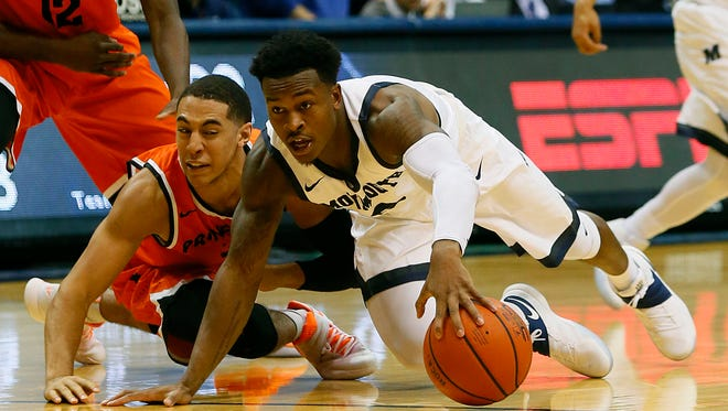 Monmouth Hawks guard Josh James (0) battles Princeton Tigers guard Devin Cannady (3) for a loose ball in December. Both teams are thinking Big Dance.