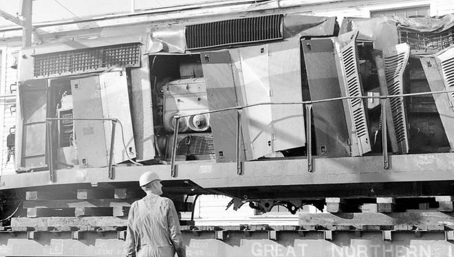 In May 1971, a  BN employee looking one of the train engines damaged at the Sheffels accident.