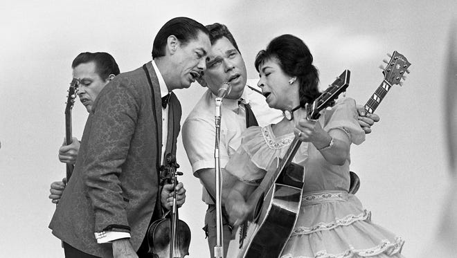 "Grand Ole Opry stars Stoney, second from left, and Wilma Lee Cooper, right, blend their voices with band member L.E. White in the familiar strains of ""Big Midnight Special"" during The Tennessean's Centennial Park concert Aug. 7, 1966."