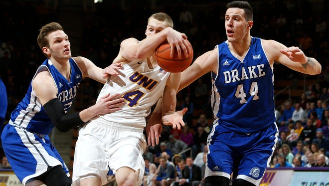 Northern Iowa's Paul Jesperson, center, drives into the lane as he is fouled by Drake's Billy Wampler, left, and defended by Dominik Olejniczak, right, in the second half Saturday, Jan. 9, 2016, in Cedar Falls, Iowa. UNI won 77-44. (Matthew Putney/The Courier via AP)
