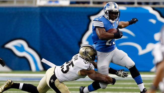 Detroit Lions running back Reggie Bush (21) is tackled by New Orleans Saints free safety Rafael Bush (25) during the first half of an NFL football game in Detroit, Sunday, Oct. 19, 2014.