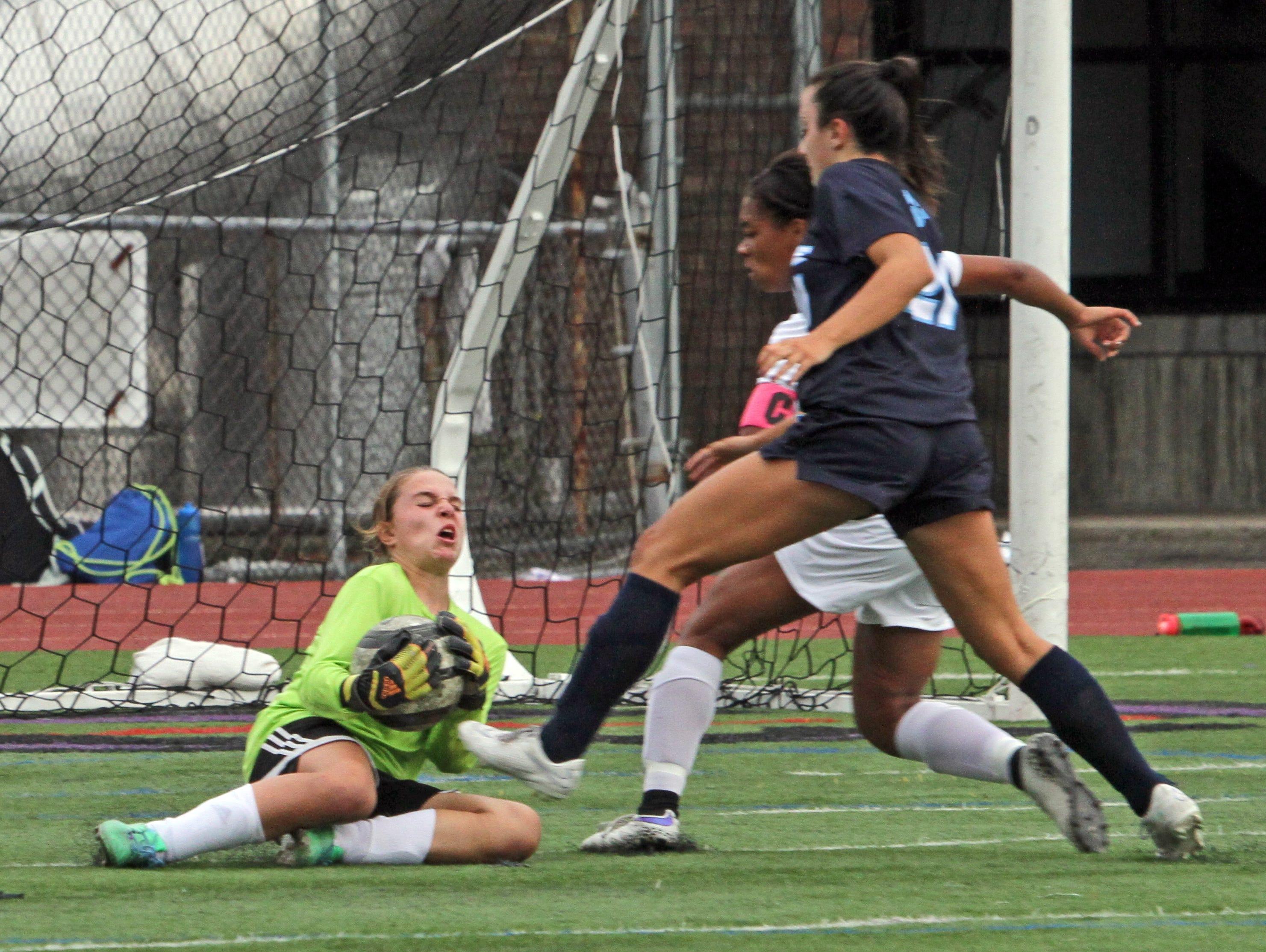 New Rochelle keeper Alexa Ostrager traps the ball as Ursuline's Julianna Sullivan bears down on her during a varsity soccer match at New Rochelle High School Sept. 30, 3015.