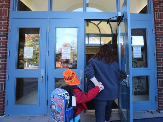 Americorps volunteer Rachel Lacer greets students getting off of the school bus at Cochran Elementary.