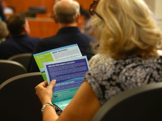 A woman reads a pamphlet on how water rates are calculated while attending a meeting about the Coachella Valley Water District's impending rate hike, June 8, 2016.