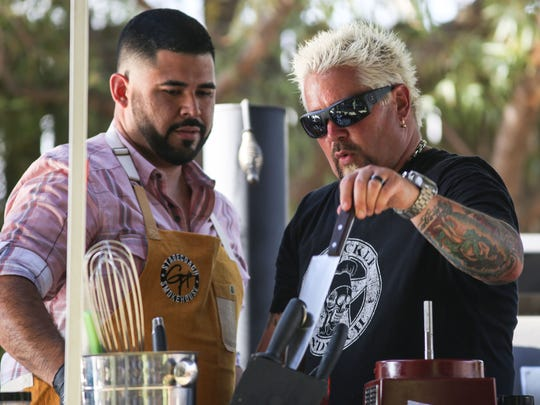 Apr 27, 2018; Indio, CA, USA; Guy Fieri, right, cooks for fans at the Stagecoach Country Music Festival at Empire Polo Club. Mandatory Credit: Jay Calderon/The Desert Sun via USA TODAY NETWORK